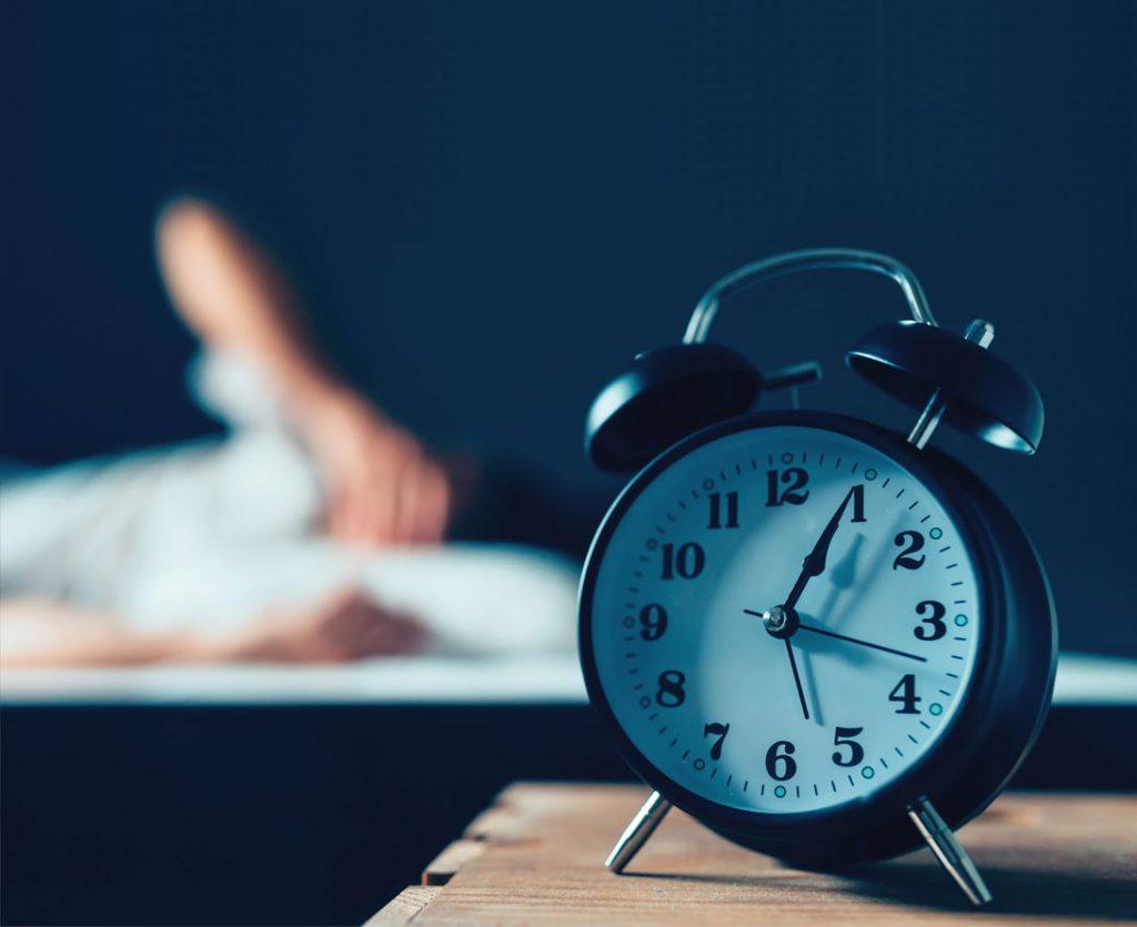 Wecker und schlaflose Person im Bett